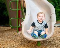 Young toddler boy child playing on slide. At playground outdoors during summer Royalty Free Stock Photo
