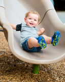 Young toddler boy child playing on slide. At playground outdoors during summer Stock Image
