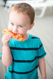 Young toddler boy on patio deck outside at sunset down at shore eating pizza. View of Young toddler boy on patio deck outside at sunset down at shore eating stock photo