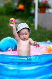 Young toddler boy playing in kiddie pool with rubber ball. Little baby playing with rubber toys in inflatable pool in the summer sunny day Royalty Free Stock Photos