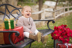 Young Toddler Child Sitting on Bench with Christmas Gifts Outside Royalty Free Stock Photo