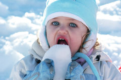 Young toddler eating snow. Caucasian young toddler with blue eyes eating snow Stock Photography