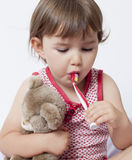 Young toddler with comforter brushing her teeth Stock Photos