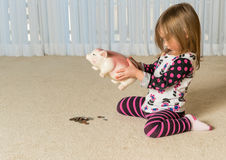 Young toddler getting money from pottery piggy bank Stock Photography