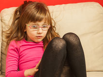 Young toddler girl in glasses sitting on sofa Royalty Free Stock Photo