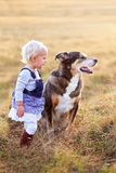 Young Toddler Girl Talking to Her Pat Dog Outside on a Fall Day stock image