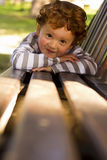 Young toddler lying on park bench Royalty Free Stock Photo