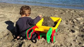 Young toddler playing with sand. And toys on a beach stock footage