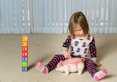 Young toddler putting money for college in bank. Young girl on floor of home saving money in a piggy bank for college educational expenses in the future Royalty Free Stock Photography