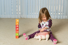 Young toddler putting money for college in bank. Young girl on floor of home saving money in a piggy bank for college educational expenses in the future Stock Image