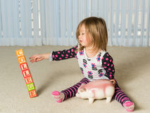 Young toddler putting money for college in bank. Young girl on floor of home saving money in a piggy bank for college educational expenses that will be out of Royalty Free Stock Image