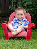 Young toddler in red chair Stock Photo