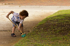 Young boy sweeping leaves from the driveway. A young toddler with red hair sweeping the leaves from the drive way Royalty Free Stock Image