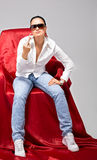 Young tomboy sit on chair - fuck sign Stock Photography