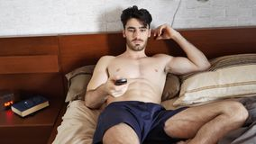 Young man waking up then turning TV on. Young topless athletic man waking up in his bed then turning TV on with remote control in the morning Stock Photography