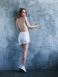 Young topless woman in white shorts and sneakers Royalty Free Stock Photography