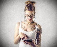 Young tough woman with tattoos reading Royalty Free Stock Images