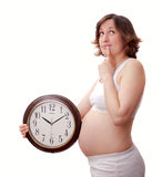 Young toughtfull pregnant woman with clock Stock Photo