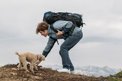 Free Young Tourist And A Dog Have Found Something Interesting In The Grass Royalty Free Stock Photography - 196357967