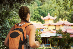Young tourist with a backpack looking into the rainforest temple Royalty Free Stock Images