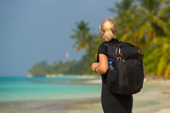 Young tourist with backpack walking in tropical beach Stock Image