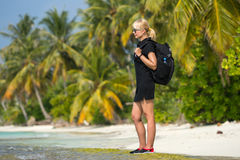 Young tourist with backpack walking in tropical beach Royalty Free Stock Images