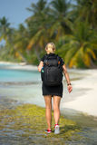 Young tourist with backpack walking in tropical beach Royalty Free Stock Photo