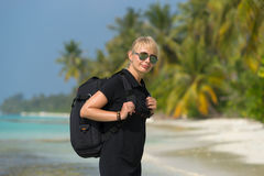 Young tourist with backpack walking in tropical beach Stock Photography