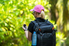 Young tourist with backpack walking in tropical jungle Stock Photos