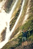 Young tourist camping with backpack near a waterfall in forest. royalty free stock image