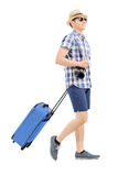 Young tourist carrying his luggage. Isolated on white background Stock Photos