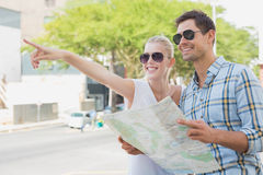 Young tourist couple consulting the map and pointing Stock Photo