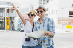 Young tourist couple consulting the map and pointing Royalty Free Stock Images