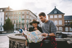 Young tourist couple exploring a city map. Royalty Free Stock Image