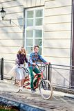 Young tourist couple, handsome man and pretty blond woman riding tandem bicycle along city street. Young active smiling traveler couple, handsome bearded men stock photo