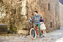 Young tourist couple, handsome man and pretty blond woman riding tandem bicycle along city street. stock photo