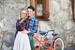 Young tourist couple, handsome man and pretty blond woman riding tandem bicycle along city street. royalty free stock image