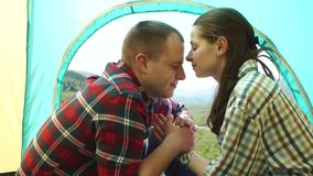Young tourist couple have a sensual moment in light tent. Beautiful young man and woman share a tender kisses stock video footage