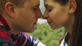 Young tourist couple have a sensual moment in tent. Beautiful young man and woman share rubbing their noses stock footage