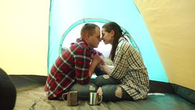 Young tourist couple have a sensual moment in tent at windy weather. Beautiful young man and woman share a tender kisses stock video