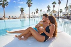 Young couple on pool hammock at beach resort. Young tourist couple on infinity pool hammock at resort on the beach drinking soda Royalty Free Stock Photos