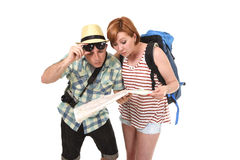Young tourist couple reading city map looking lost and confused loosing orientation with girl carrying travel backpack Royalty Free Stock Images