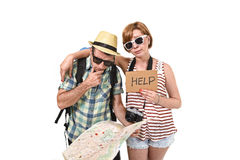 Young tourist couple reading city map looking lost and confused loosing orientation with girl carrying travel backpack. And men in frustrated face expression Royalty Free Stock Photos