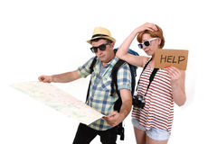 Young tourist couple reading city map looking lost and confused loosing orientation with girl carrying travel backpack Stock Images