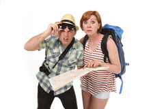 Young tourist couple reading city map looking lost and confused loosing orientation with girl carrying travel backpack Royalty Free Stock Photo