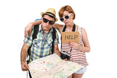 Young tourist couple reading city map looking lost and confused loosing orientation with girl carrying travel backpack Stock Image