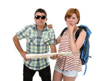 Young tourist couple reading city map looking lost and confused loosing orientation with girl carrying travel backpack Royalty Free Stock Photography