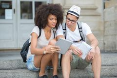 Young tourist couple reading online city guide before tour. Young royalty free stock images