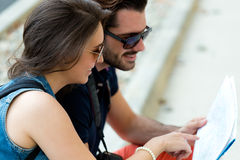 Young tourist couple in town holding a map. Royalty Free Stock Photography