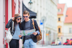 Young tourist couple traveling on holidays outdoors smiling happy. Caucasian family with city map in search of. Happy tourist couple, men and women traveling on royalty free stock photography